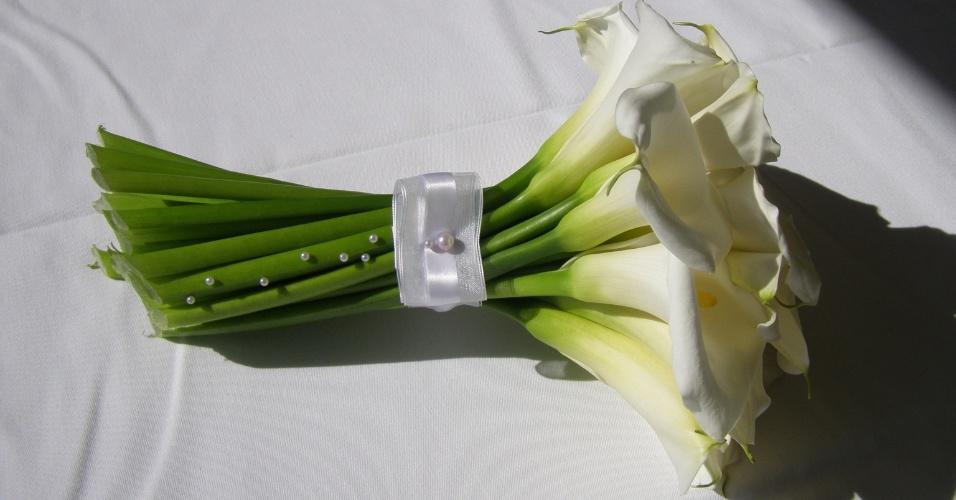 Buquê de copo-de-leite com haste envolta por fita branca e aplicações de pérolas ao longo das hastes