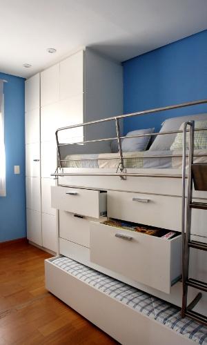 O projeto do móvel idealizado para o quarto de um menino de sete anos, pela arquiteta Cristiane Schiavoni, aproveitou o vão entre as camas para dispor gavetas de diversos tamanhos. Na sequência do mobiliário está o armário que vai do piso ao teto e possui três portas