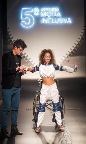 19.nov.2013 - Modelo com deficiência física se levanta da cadeira de rodas para mostrar a criação do participante Arthur Vicent de Moura Del Nery