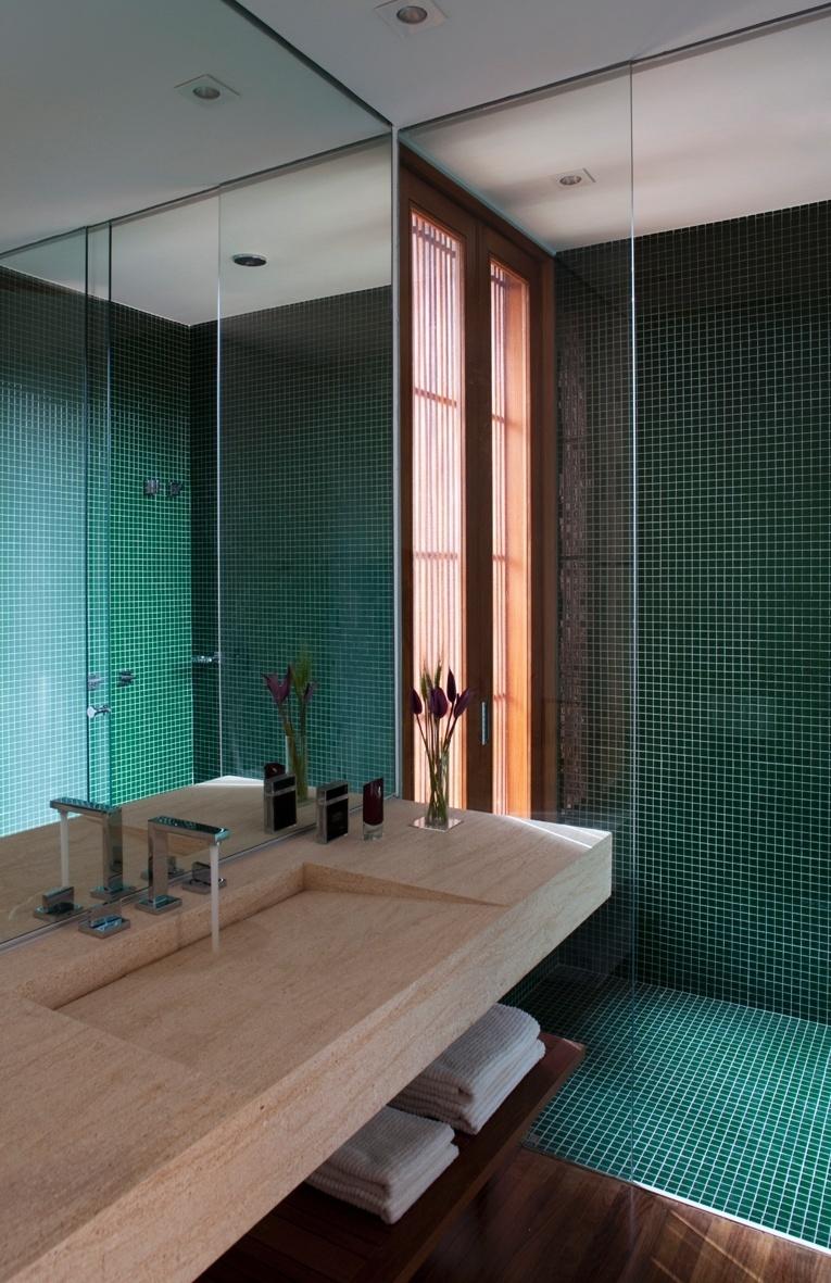Os banheiros da casa M.A.N., com design do escritório Gálvez & Marton Arquitetura, tem box revestido por pastilhas de vidro Vitrocolori, piso de madeira cumaru (Marcenaria Hydrotec) e pias em mármore travertino polido (Pedras Ipiranga)