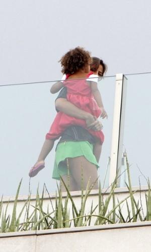 24.nov.2013 - Paula Moraes, namorada do ex-jogador Ronaldo, segura filha do empresário durante almoço para família em sua cobertura no Leblon, no Rio