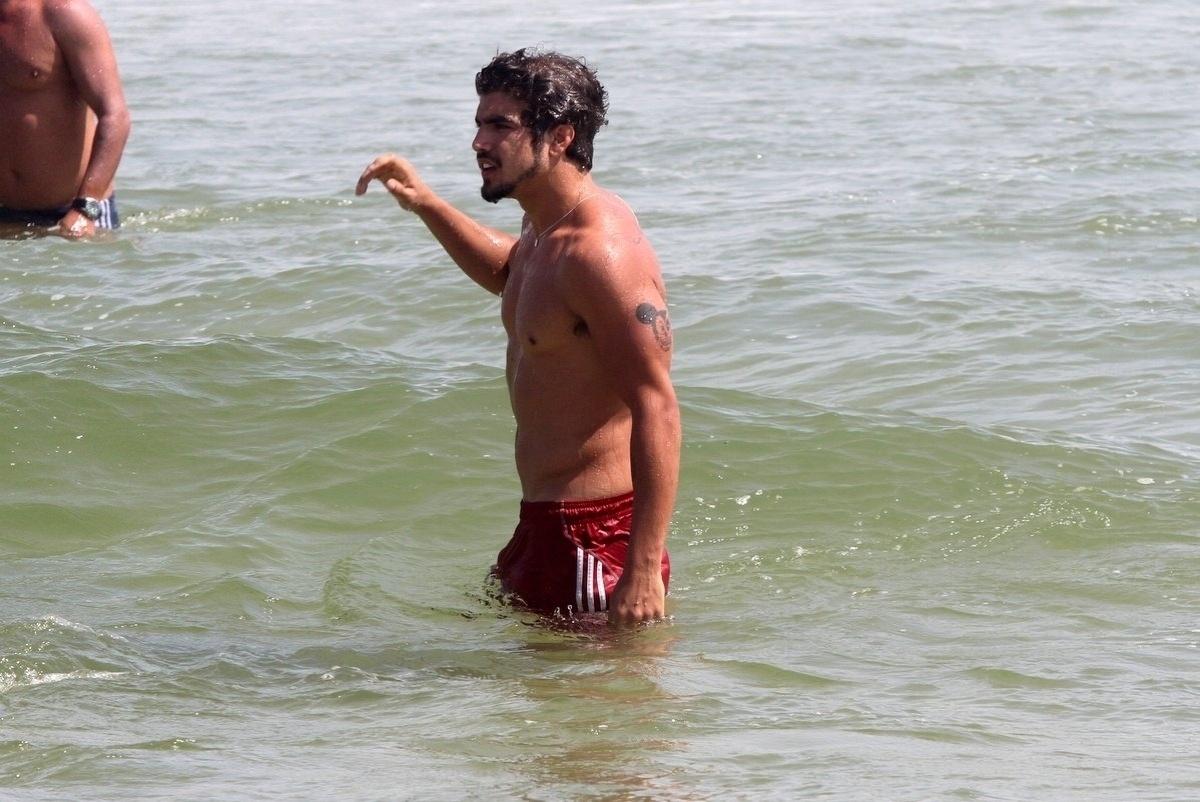 05.dez.2013- Caio Castro se refresca no mar e exibe corpo em forma