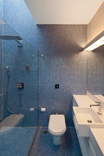 A iluminação dos banheiros se dá através de dois planos da laje de cobertura. Piso e paredes em pastilhas azuis contrapõem com o branco da bancada e das louças sanitárias. A Casa Bacopari tem projeto arquitetônico assinado pelo Grupo Una