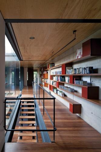 A galeria de circulação entre os dormitórios foi aproveitada como biblioteca da família. Piso e forro em madeira contrastam com o vigamento metálico. A Casa Bacopari tem projeto arquitetônico assinado pelo Grupo Una