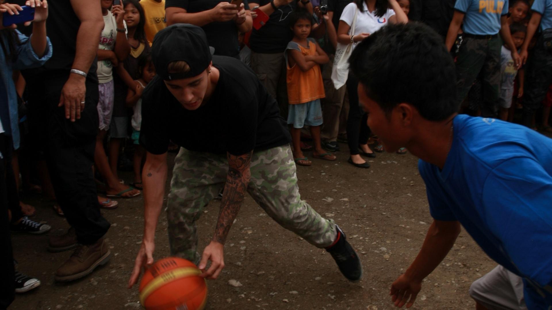 10.dez.2013 - O cantor Justin Bieber joga basquete com alunos sobreviventes do tufão Haiyan em escola de Tacloban, nas Filipinas