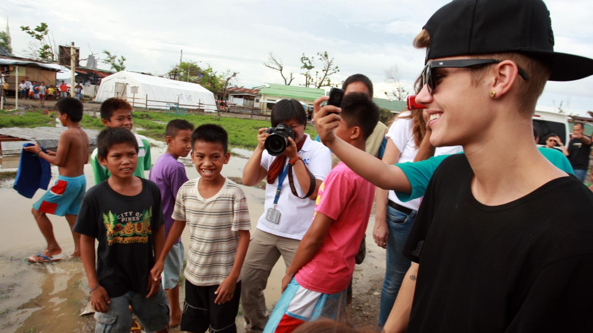 10.dez.2013 - O cantor Justin Bieber visita uma escola com sobreviventes do tufão Haiyan, que atingiu as Filipinas em novembro