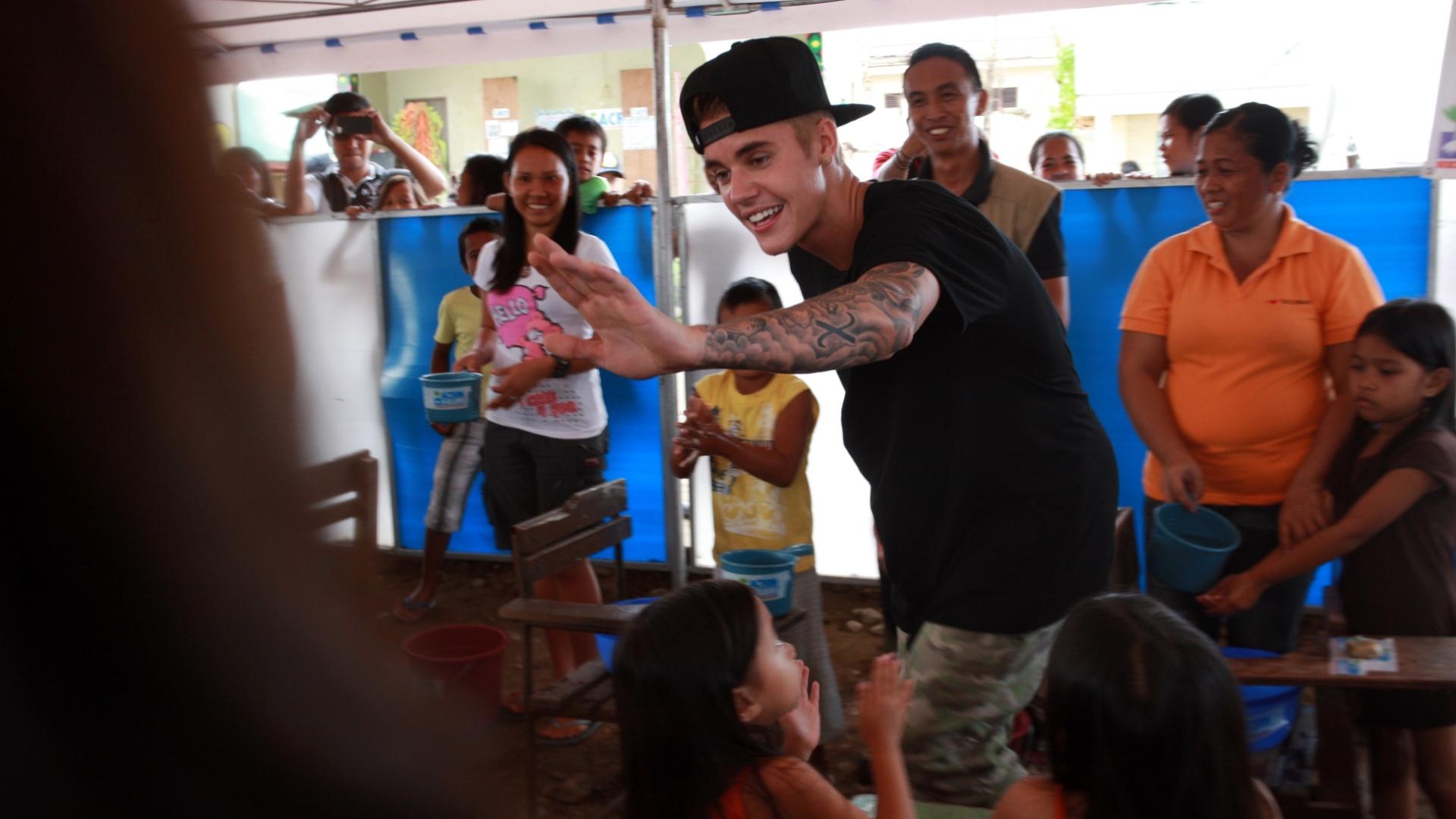 10.dez.2013 - O cantor Justin Bieber visita uma escola nas Filipinas e canta a música