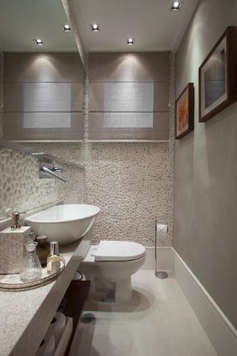 No lavabo, a arquiteta Fernanda Pinheiro combinou o cimento queimado em parte das paredes (tom acinzentado) e no piso (pintado de branco) com os seixos telados que em uma das paredes laterais e em parte da superfície acima da bancada. Essa mistura de revestimentos traz leveza ao ambiente