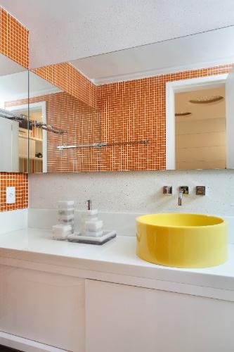 Para quebrar com o branco da bancada do banheiro, as arquitetas Claudia Pimenta e Patricia Franco escolheram uma cuba em amarelo claro e aplicaram pastilhas alaranjadas em parte das paredes