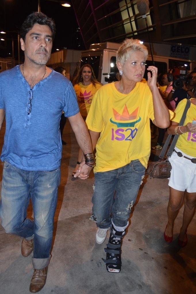 14.dez.2013 - Xuxa e o namorado, Junno Andrade, chegam à gravação do DVD em comemoração aos 20 anos de carreira de Ivete Sangalo na Arena Fonte Nova, em Salvador. A apresentadora está usando uma bota ortopédica há quase um mês, quando sofreu uma queda durante a gravação de seu programa