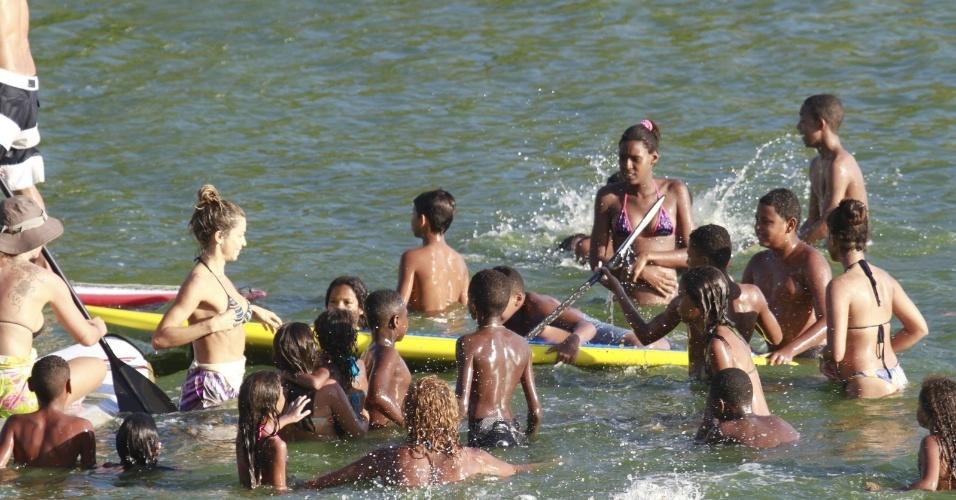 8.jan.2014 - Grazi Massafera pratica stand up paddle, na praia da Barra da Tijuca, no Rio, e é cercada por fãs