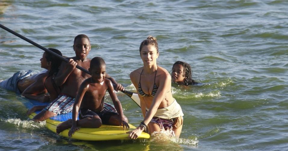 8.jan.2014 - Grazi Massafera pratica stand up paddle, na praia da Barra da Tijuca, no Rio, e se diverte com crianças