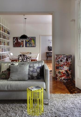 A mesa de apoio Kub (Poeira), de metal com pintura amarela, pontua com cor vibrante a sala de estar equipada com sofá de linho cinza e tapete na mesma tonalidade (ambos da Novo Ambiente). A decoração do apartamento alugado no bairro do Leblon, Rio de Janeiro (RJ), é um projeto do trio de arquitetas Roberta Moura, Paula Faria e Luciana Mambrini