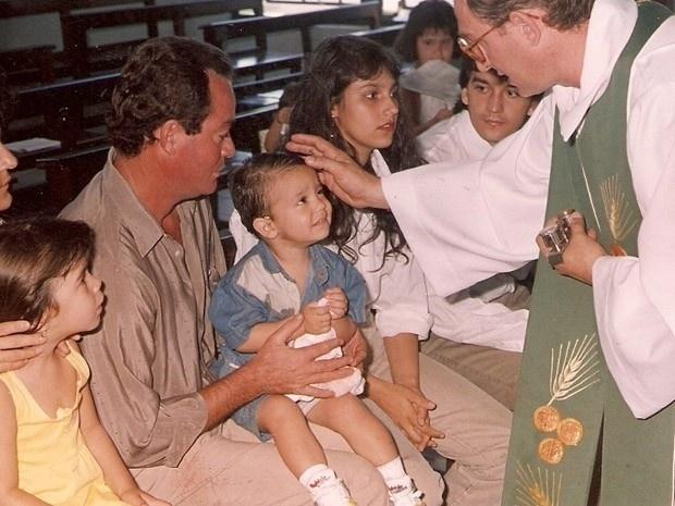Luan recebendo a benção de um padre