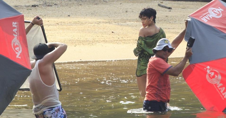 """13.jan.2014 - Em Angra dos Reis, no Rio de Janeiro, Rihanna fotografa para a revista """"Vogue Brasil"""" sem a parte de cima do biquíni e de chapéu"""