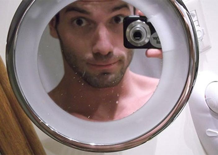 Roni faz graça no espelho do banheiro do hotel onde está confinado
