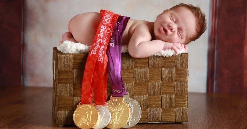 15.jan.2014 - Primeiro filho dos jogadores de vôlei Jaqueline e Murilo, Arthur posa com as medalhas conquistadas pelos pais nas Olimpíadas de Londres e Pequim, em 2012 e 2008. No dia em que as fotos foram tiradas, Arthur, que nasceu no dia 19 de dezembro, tinha apenas 23 dias de vida e media 56 cm