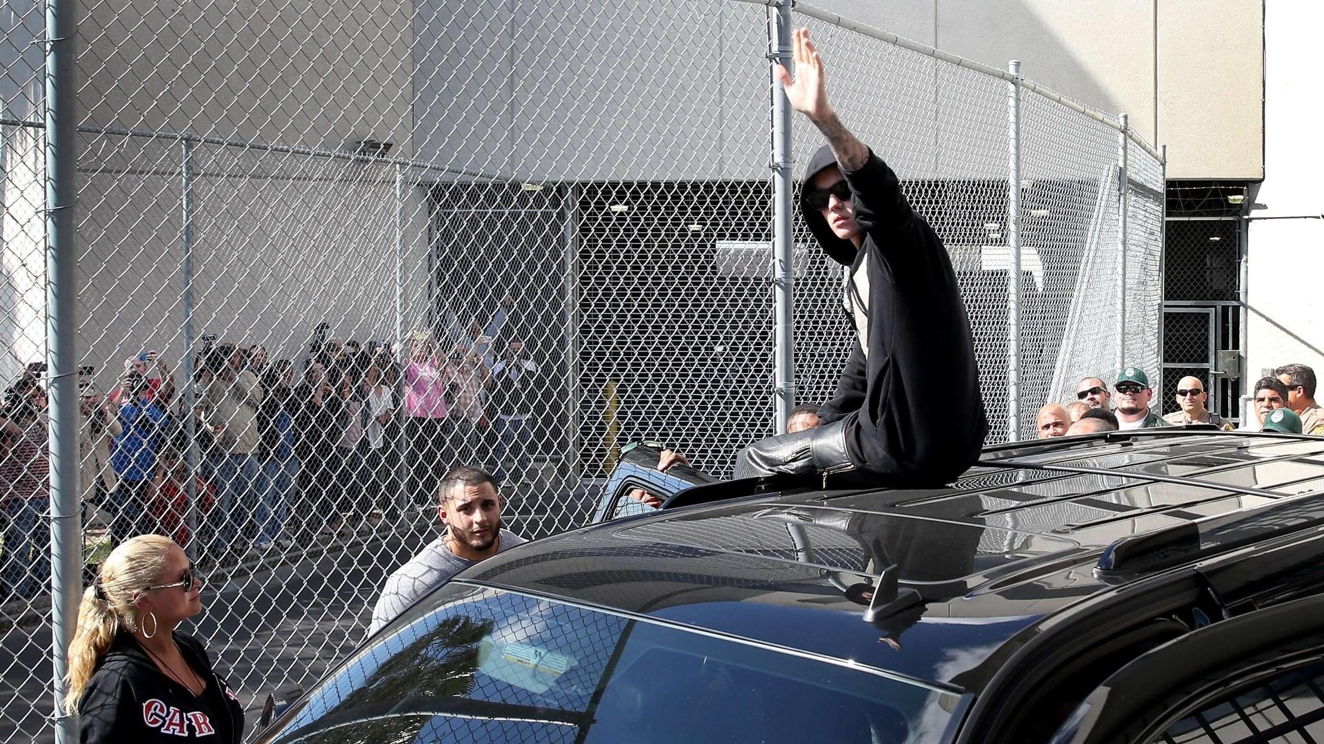 23.jan.2014 - Justin Bieber deixou a prisão após comparecer à primeira audiência, no Centro de Correção Turner Guilford Knight, em Miami. 23.jan.2014 - Justin Bieber deixou a prisão após comparecer à primeira audiência, no Centro de Correção Turner Guilford Knight, em Miami. O cantor foi preso por dirigir alcoolizado. A emissora de TV americana NBC filmou o momento e exibiu quando o cantor acenou para os jornalistas do topo de um carro