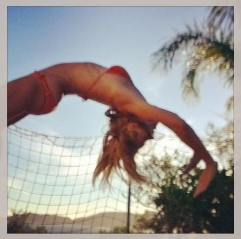 29.jan.2014 - De biquíni, Carolina Dieckmann se diverte em cama elástica e mostra barriga chapada