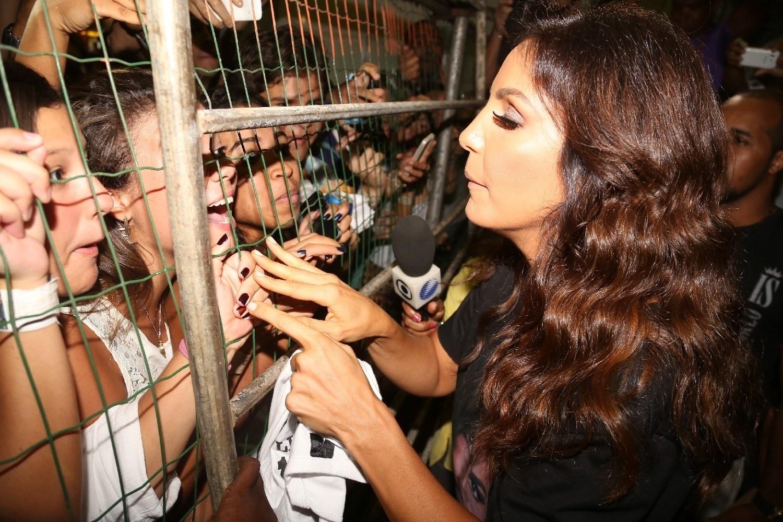 30.jan.2014 - A cantora atendeu alguns fãs mesmo com uma cerca separando eles