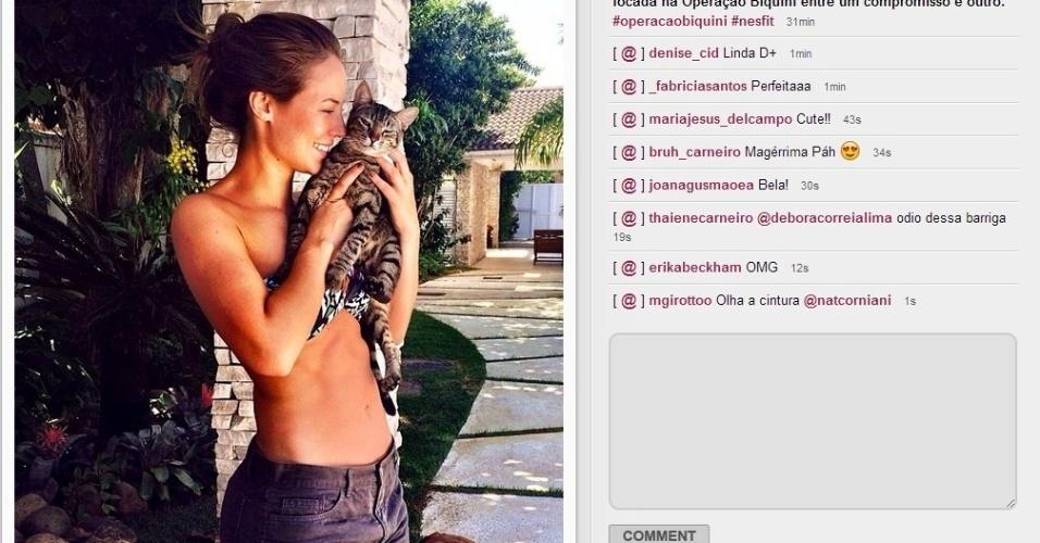 04.fev.2014 - De biquíni e short, Paolla Oliveira brinca com seu gato e publica a imagem em sua conta no Instagram. A atriz, que está de férias depois de