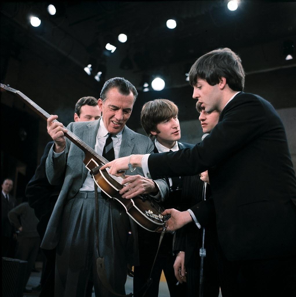 09.fev.1964 - Paul McCartney mostra seu baixo ao apresentador Ed Sullivan nos bastidores do programa