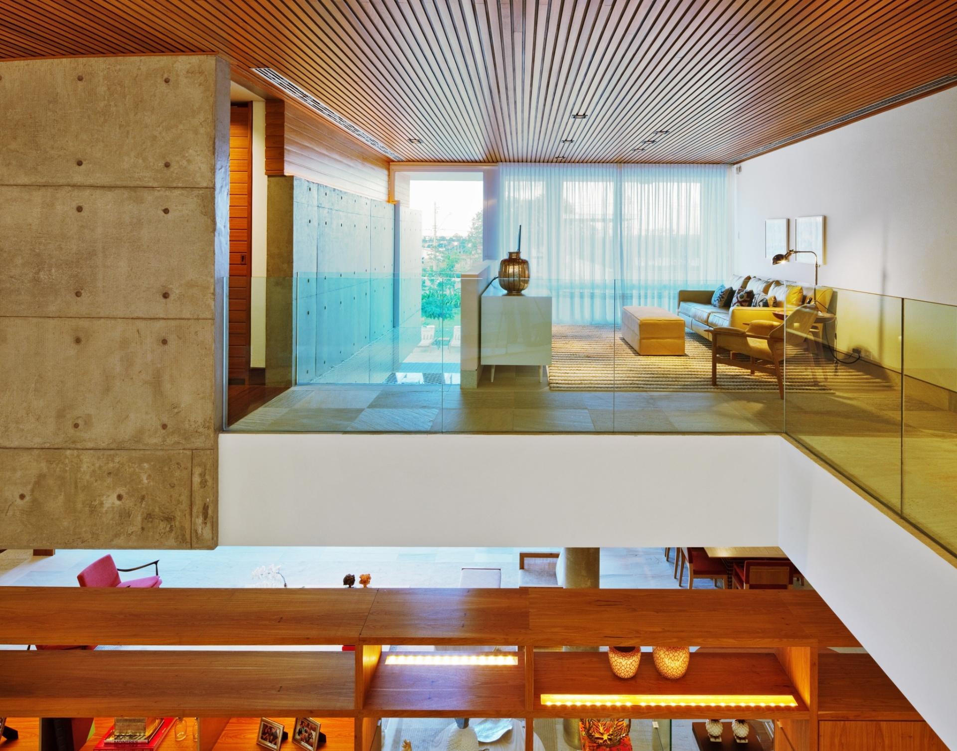 No pavimento superior, uma saleta íntima precede o corredor de acesso aos dormitórios. Esse espaço possui atmosfera acolhedora e é muito usado pela família. Destaque para a mescla harmônica de materiais, como concreto, madeira, pedra e vidro. A Casa FG foi projetada pelo escritório Reinach Mendonça Arquitetos Associados