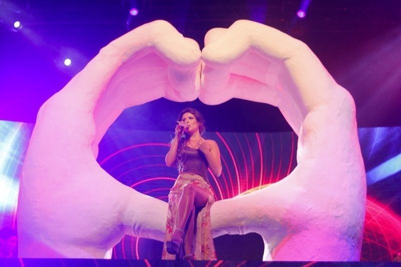 Paula Fernandes sentada nas mãos gigantes que fazem parte da turnê