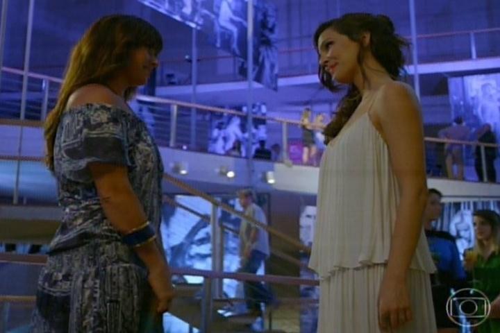 13.fev.2014 - Durante sua exposição de fotos, Marina (Tainá Mülher) se interessa por Clara (Giovanna Antonelli) assim que a moça chega com Cadu (Reynaldo Gianecchini). Encantada, ela se aproxima de Clara e puxa conversa