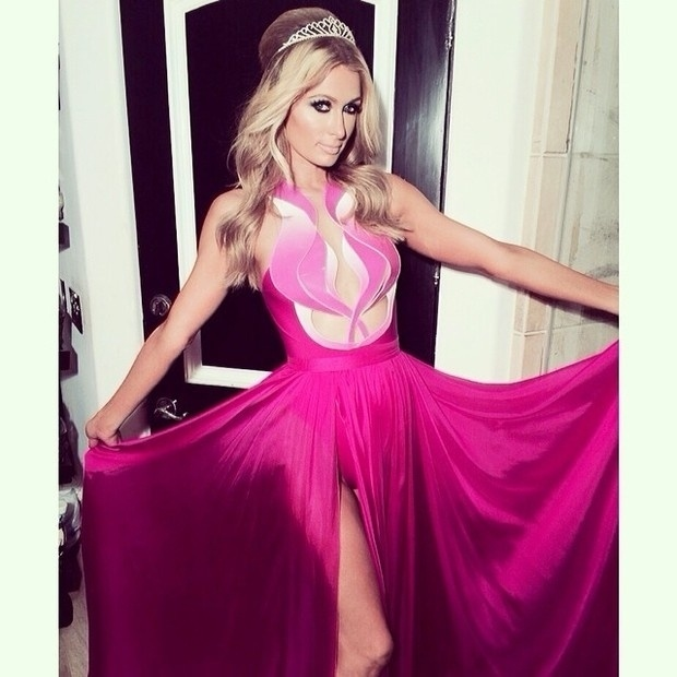 16.fev.2014 - Para comemorar seus 33 anos, a patricinha Paris Hilton escolheu um vestido rosa com uma fenda gigante na parte frontal. Abaixo do decote é possível ver um body que  diminui a ousadia do look