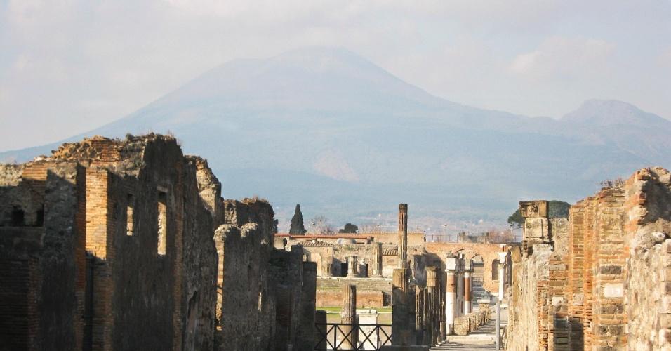 Vista geral de uma parte do sítio arqueológico de Pompeia, com o imponente vulcão Vesúvio ao fundo, dominando o horizonte da antiga cidade