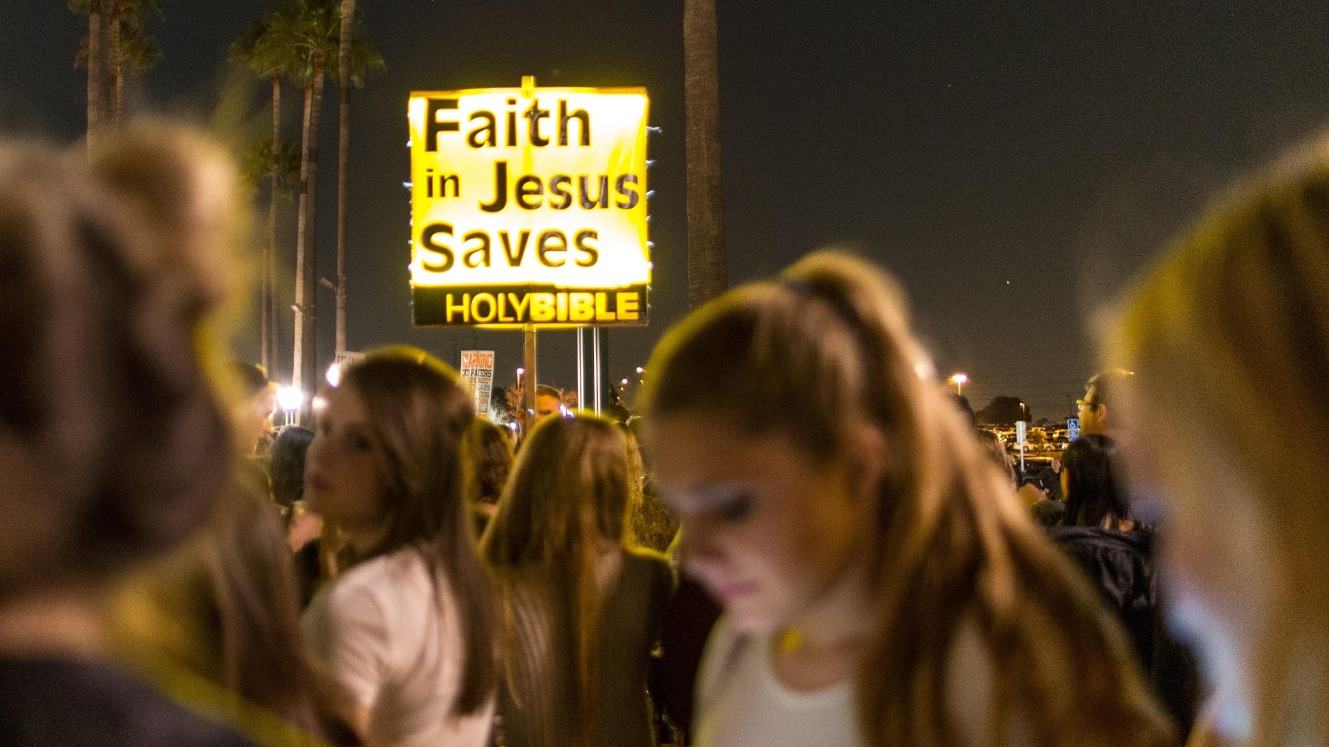 21.fev.2014 - Manifestantes posicionam placas religiosas em frente à casa de shows que recebeu a turnê