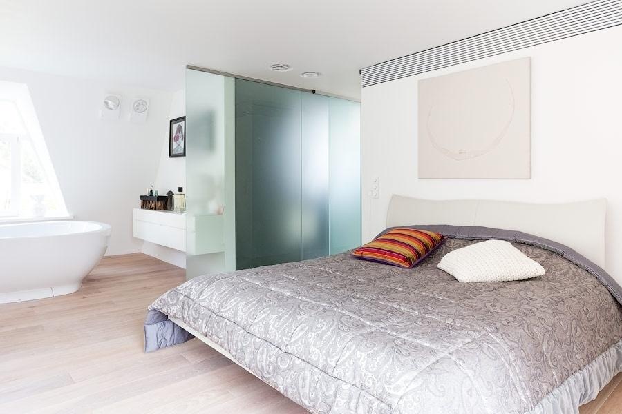 A suíte do casal, no primeiro pavimento da casa N, é um espaço íntimo de privacidade e recolhimento. Completo, o dormitório é francamente aberto à banheira e conta com sala de ducha - esta separada por porta de correr de vidro jateado - e closet. O projeto integrador de reforma é do escritório alemão 4a Architekten