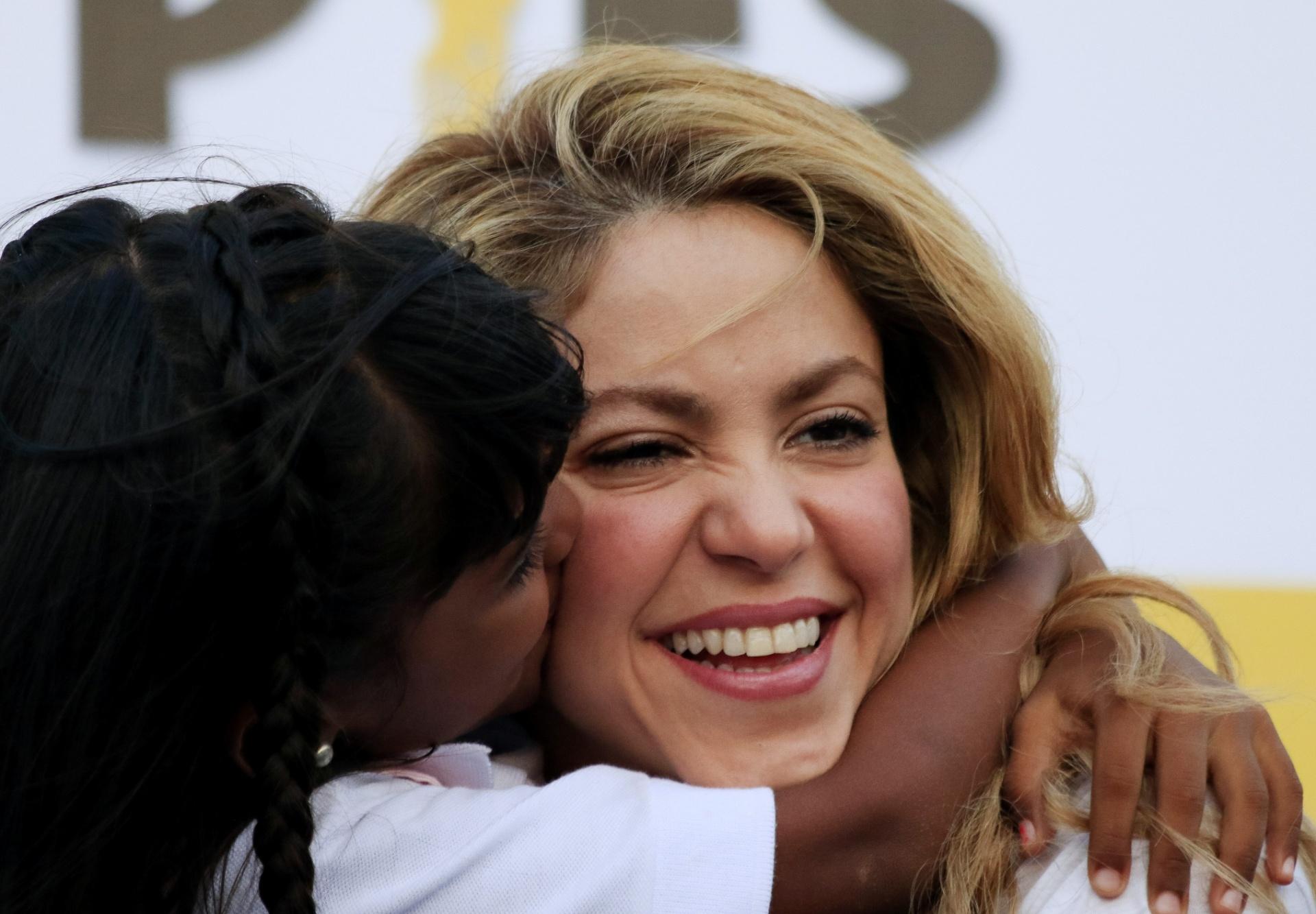 24.fev.2014 - Shakira recebe o carinho de uma criança durante a inauguração de uma escola em Cartagena, na Colômbia