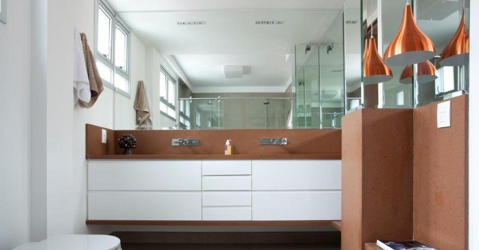 Nesse banheiro, o silestone (composto de quartzo, resina de poliéster e pigmento) foi usado tanto na bancada da pia quanto na parede. O tom terroso aliado à luminária pendente de cobre, instalada estrategicamente junto a uma parede espelhada, foram os responsáveis por deixar a decoração mais aconchegante. O projeto é da arquiteta Claudia Macedo