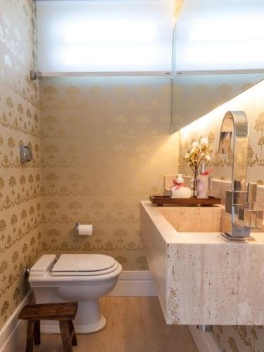 O lavabo ficou muito mais aconchegante com a aplicação do papel de parede escolhido pela arquiteta Vivi Cirello, cujos tons se alinharam bem ao mármore usado na bancada da pia. Persiana rolô cobriu o espaço da janela