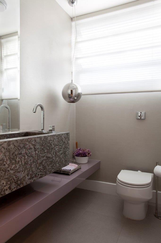 Para cobrir a janela do lavabo, a arquiteta Claudia Macedo optou por utilizar uma cortina rolô, que mantém a privacidade da área e permite que a luz entre. Outro destaque da decoração é o pendente de vidro instalado sobre a prateleira baixa de laca brilhante lilás