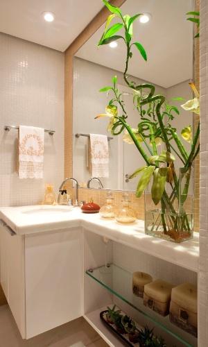 Um vaso de vidro com antúrios e bambus da sorte decora a bancada da pia desse lavabo. Sob o tampo, prateleiras também de vidro servem de apoio para velas, cactos e suculentas. O projeto é do arquiteto Luís Fábio Rezende de Araújo