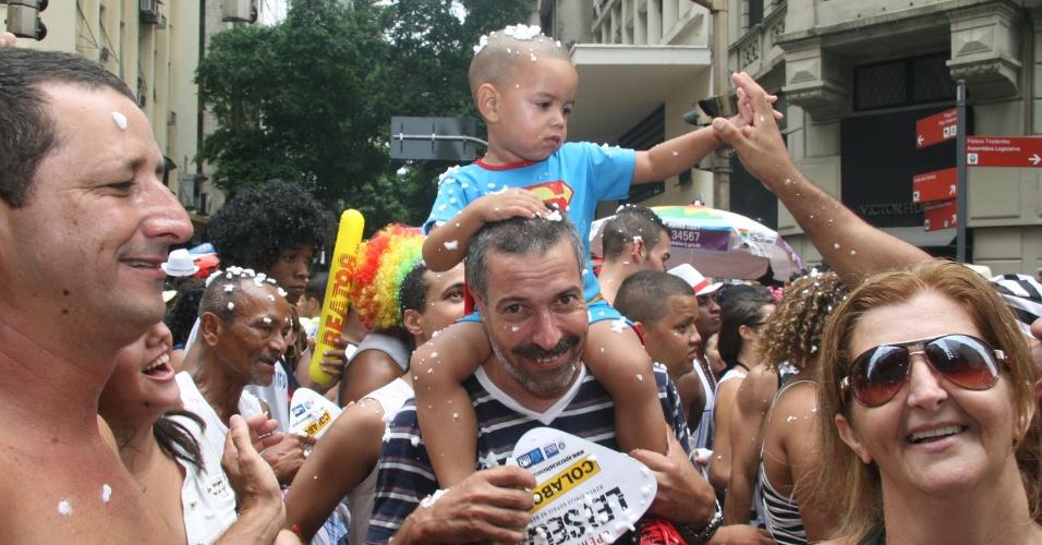1.mar.2014 - Com o filho nos ombros, folião se diverte no bloco Cordão da Bola Preta, no centro do Rio de Janeiro