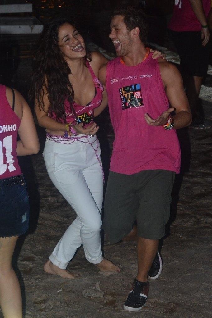 2.mar.2014 - Descalça, Nanda Costa dança na areia com o ator Leonardo Miggiorin durante show da banda Moinho no Camarote Salvador