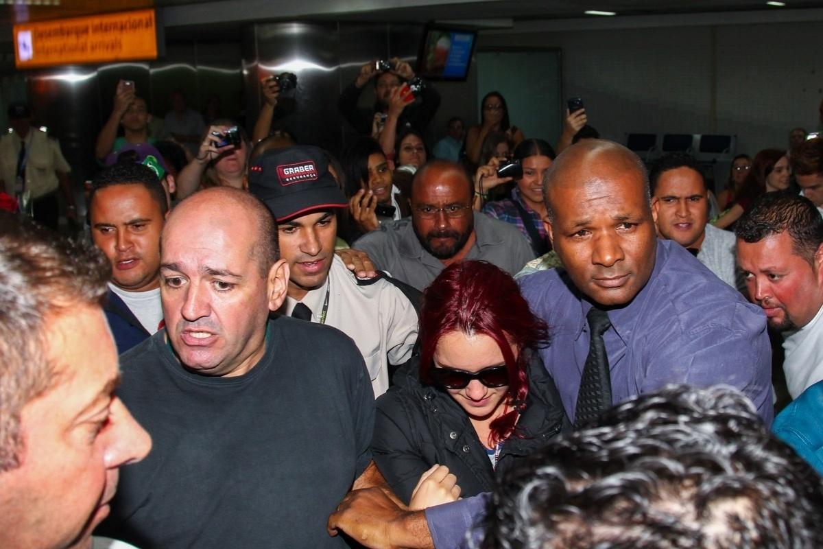 06.mar.2014- Cercada por seguranças, a chegada de Dulce María ao Brasil foi marcada por tumulto, empurrões, cartazes e gritos histéricos de fãs