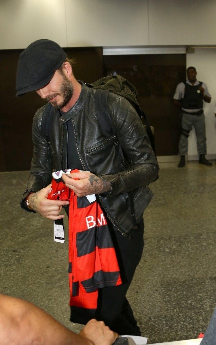 6.mar.2014 - No Brasil para assistir aos desfiles das escolas campeãs do Rio de Janeiro, o jogador de futebol David Beckham distribui autógrafos ao desembarcar na cidade carioca
