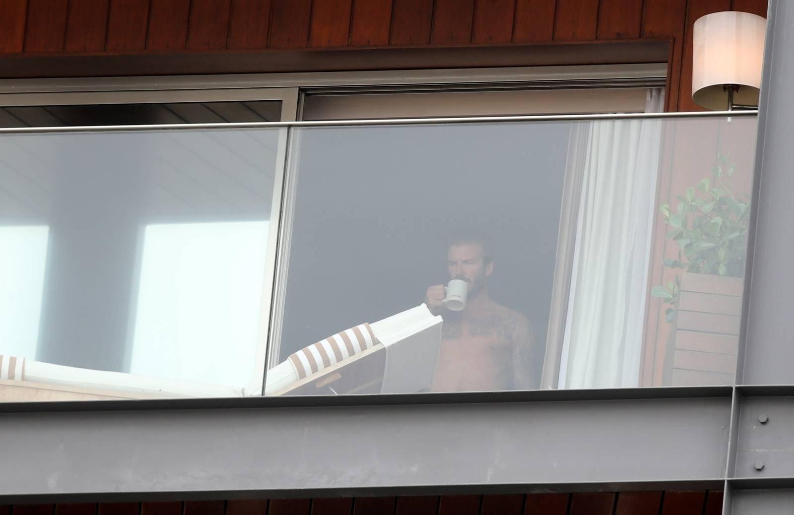 6.mar.2014 - No Brasil para assistir aos desfiles das escolas campeãs do Rio de Janeiro, o jogador de futebol David Beckham é flagrado sem camisa e com uma xícara nas mãos, na sacada do hotel onde está hospedado, na zona sul da cidade
