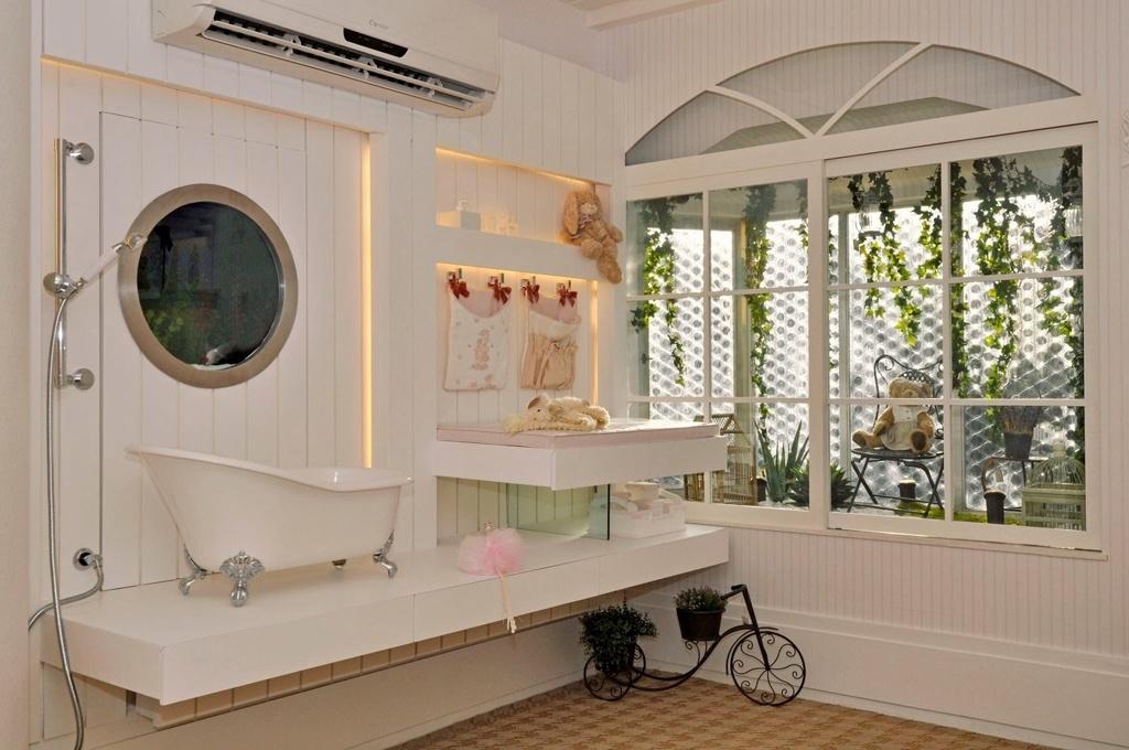 A arquiteta e urbanista Magaly Gentil montou um cantinho para a higiene do bebê em um quarto com estilo provençal. Sobre a bancada de madeira com pintura grofatto há uma pequena banheira em estilo vitoriano, de cerâmica e com pés de ferro, um clássico dos antigos apartamentos europeus. Já o painel de madeira lembra uma