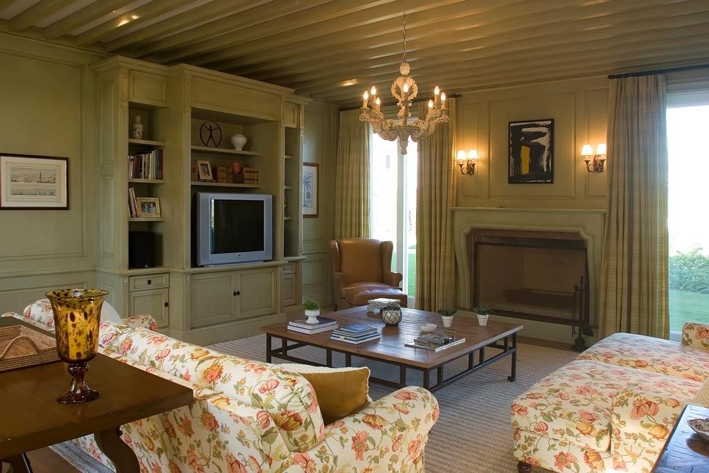 Na sala da família (46,8 m²), o arquiteto Leonardo Junqueira reforçou o clima campestre com a boiserie (revestimento de parede em madeira, com