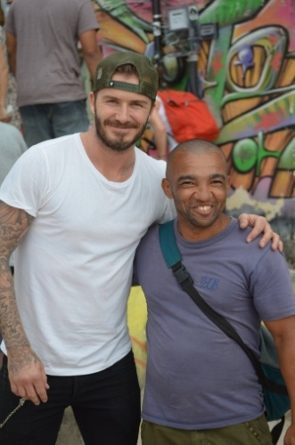 6.mar.2014 - No Brasil para assistir aos desfiles das escolas campeãs do Rio de Janeiro no próximo sábado (8), o jogador de futebol David Beckham visitou a favela do Vidigal e posou com os moradores para fotos, além de segurar crianças no colo
