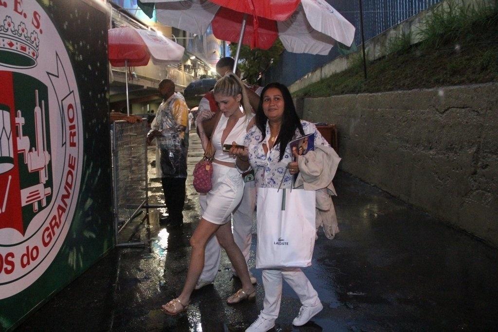 8.mar.2014 - Bárbara Evans chega debaixo de chuva para o desfile das campeãs no Rio. A modelo irá desfilar na Grande Rio, na noite deste sábado (8)