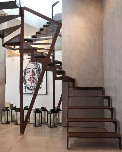 O hall da escada que liga os pavimentos exibe uma coleção de lamparinas pertencentes ao morador. A escada em aço corten (liga de aço, nióbio e cromo, resistente à maresia) entra em sintonia com o cimento queimado aplicado à parede. A cobertura Rio Design Leblon tem projeto de reforma assinado pelo escritório House in Rio