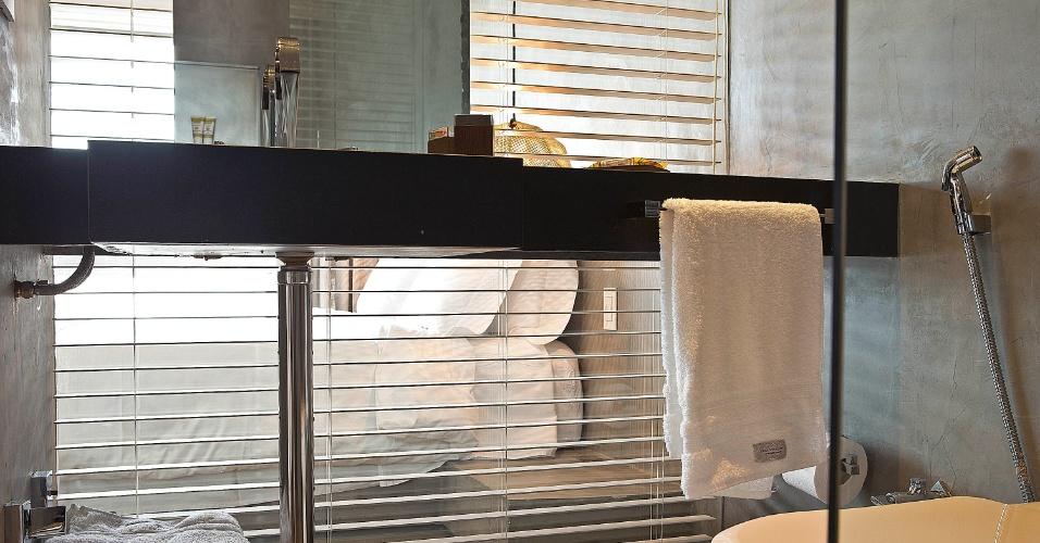 Com a persiana aberta é possível enxergar o dormitório através do vidro, único elemento a limitar os ambientes do quarto e do banheiro. A solução permitiu que a partir do banheiro fosse possível a visualização da paisagem do Rio, através janela do quarto. A cobertura Rio Design Leblon tem projeto de reforma assinado pelo escritório House in Rio
