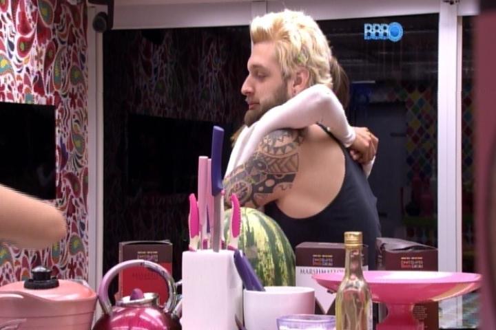 21.mar.2014 - Cássio ganha um abraço inusitado de Angela antes do jantar. A sister pulou nos braços do brother na cozinha enquanto os outros confinados faziam o jantar